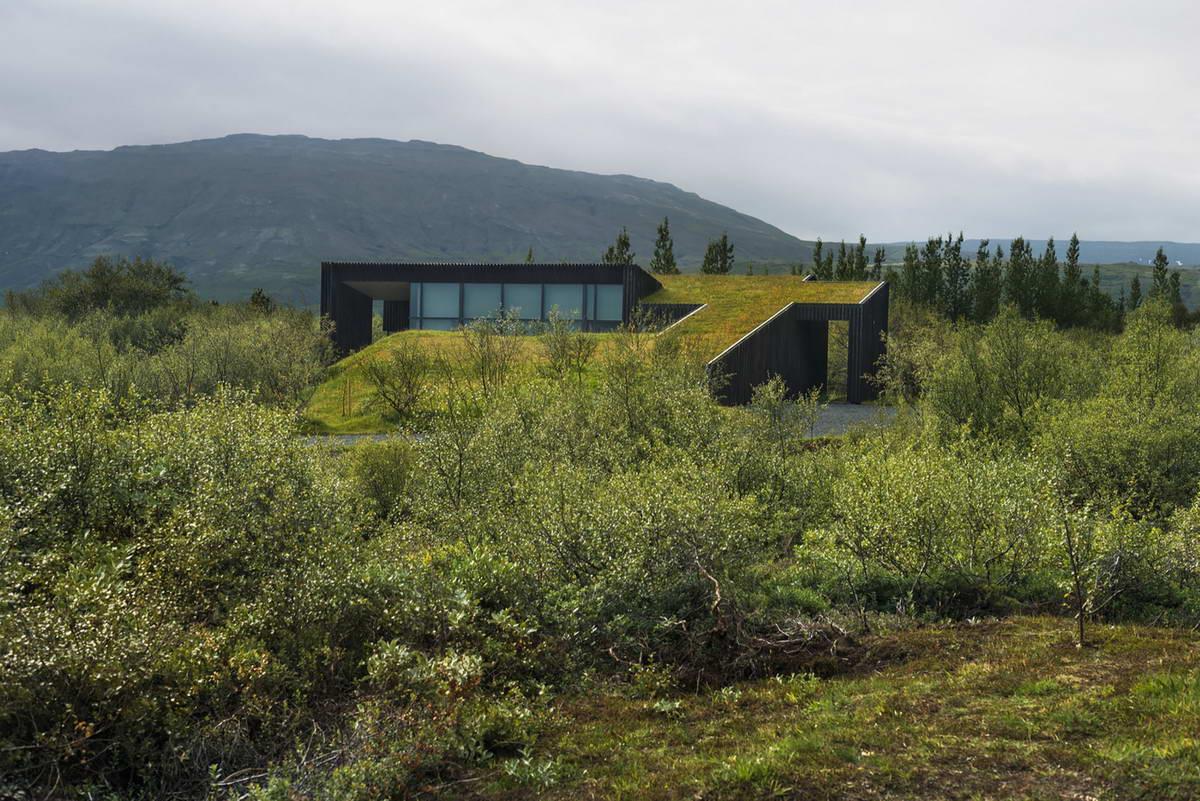 Дом с зелёной крышей и обугленными фасадами